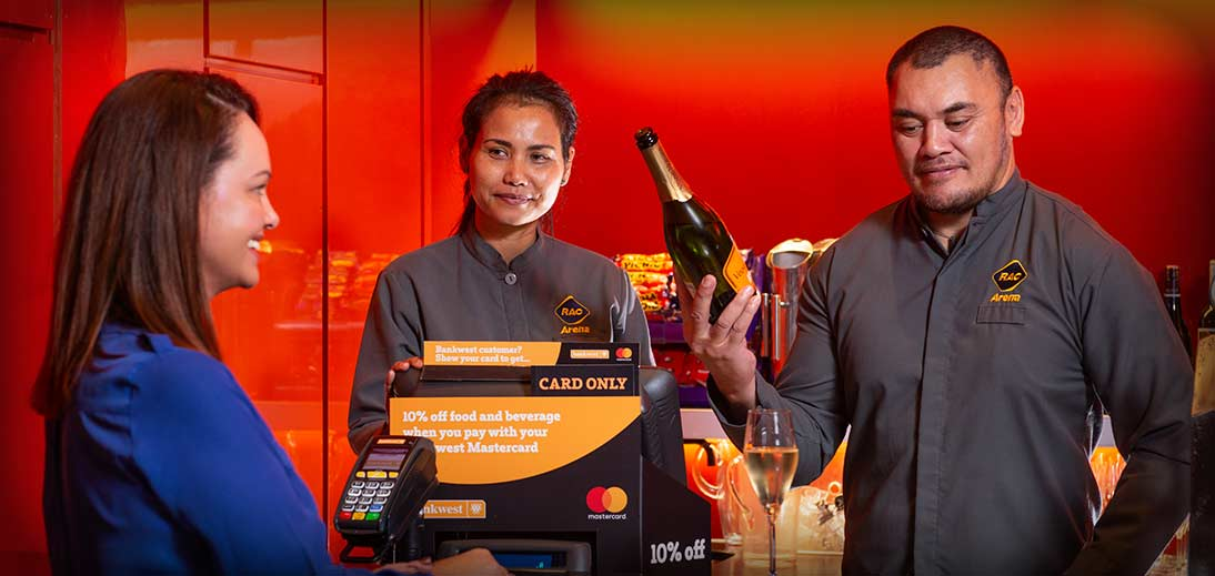 Image of two cashiers serving a patron a glass of champagne