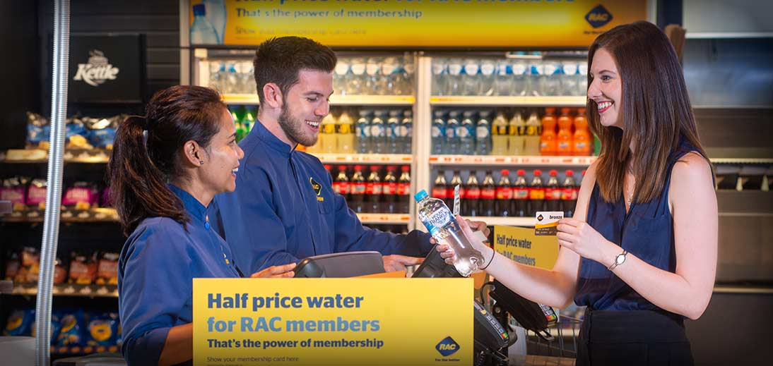 Image of a patron purchasing a bottle of water from two cashiers, showing their RAC membership