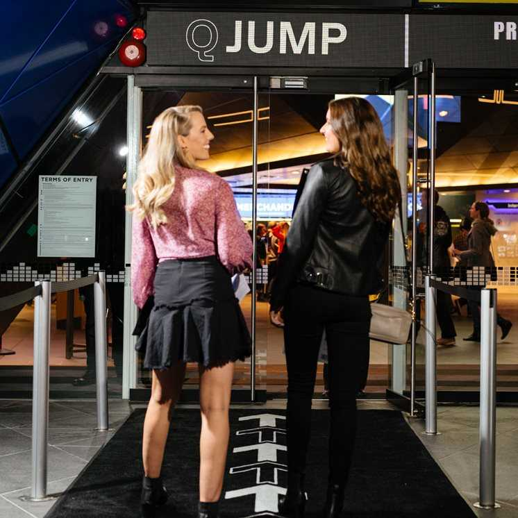 Two female patrons smile as they use the Q Jump fast lane